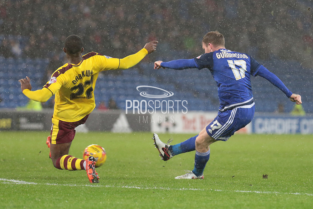 Burnley defender Tendayi Darikwa tries to block Cardiff City midfielder Aron Gunnarsson's attempt on goal during the Sky Bet Championship match between Cardiff City and Burnley at the Cardiff City Stadium, Cardiff, Wales on 28 November 2015. Photo by Jemma Phillips.