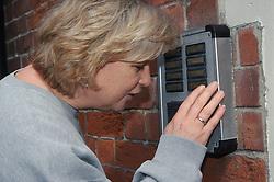 Woman speaking into door intercom,