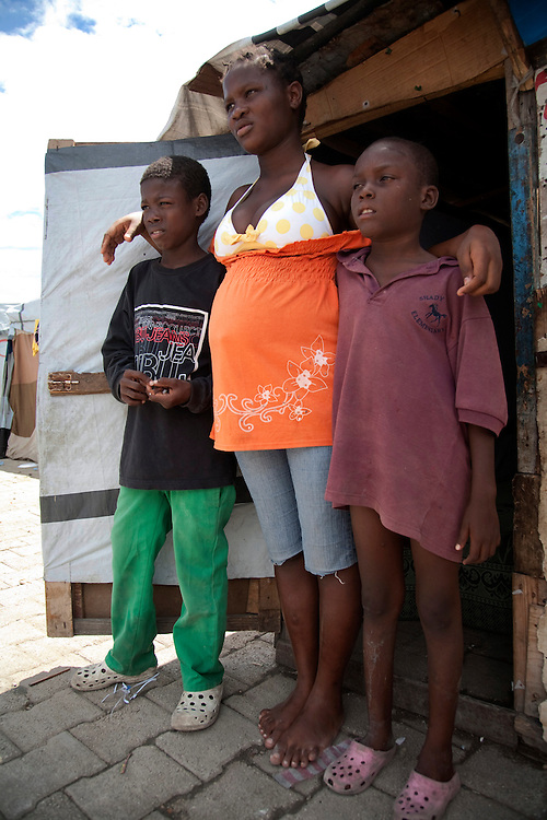 Ema Yanick, 16 years-old,who is pregnant and taking care of her two brothers, her 2 brothers Giovanni, 7 year- old, Junior,13 year-old, after losing her parents in the Haiti earthquake, in the makeshift refugee camp, La Piste, in Port-au-Prince, Haiti on July 18, 2010. <br /> <br /> La Piste (French for &quot;runway&quot;)is a settlement sprawled across the site of a disused airport and now home to an estimated 20,000 earthquake survivors living in makeshift structures.<br /> Six month after a catastrophic earthquake measuring 7.3 on the Richter scale hit Haiti on January 13, 2010, killing an estimated 230,000 people, injuring an estimated 300,000 and making homeless an estimated 1,000,000.