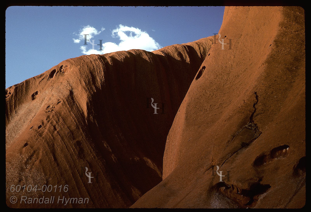 Red sandstone walls sweep skyward against deep blue sky of late afternoon; Uluru Natl Park. Australia