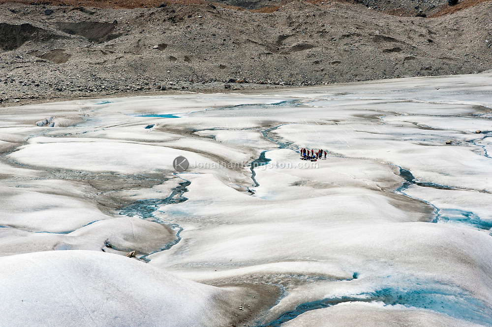 A group of tourists is dwarfed by the glacier on which they stand.