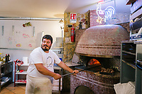 NAPLES, ITALY - 1 AUGUST 2018: Roberto bakes a pizza in the oven at Cantina del Gallo, a family-owned restaurant in the Rione Sanità in Naples, Italy, on August 1st 2018.<br /> <br /> Cantina del Gallo, in the Rione Sanità, was established in 1898 and run by four generations of the Silvestri family. The cantina began as a store selling bulk wine and oil. It was only in the 1950s, when the legendary Aunt Cuncetta began cooking, that it became the simple and genuine tavern it is today.<br /> There are three dishes that are the restaurant's workhorses, and the ones we always seem to rotate between: the pennette alla sorrentina (a variation of the classic gnocchi alla sorrentina, seasoned with tomato, basil and stringy mozzarella), the baked cod (although the fried cod is just as mouth-watering) and the pizza cafona (peasant pizza), topped with oregano, cheese, chile and with double the tomatoes (tomato juice and chopped tomatoes).