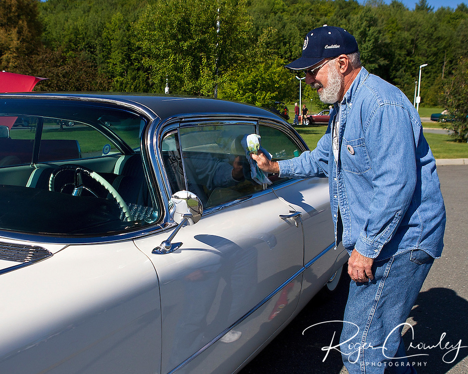 BARTON VT - 144th Orleans County Fair in the scenic Northeast Kingdom village of Barton, Vermont broke the Guinness World Records of the longest Cadillac Parade in history with 298 cars Wednesday in Barton Vermont. Sal Santoro of New Jersey polishes his vintage Cadillac before the parade..