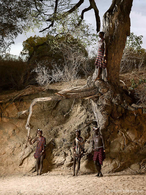 Kala, Daina, Kale and Oita pose for a portrait under the roots of a huge tree on a dry river bed at sunset in the Lower Omo Valley.<br /> <br /> The rains are late this year but even when the rains come, they no longer fill the river to the levels of the top root.
