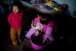 Eli Cordoba bathes her daughter Lucera as her other daughter Angela stands by. Both Lucera and Angela have severe lead poisoning, with quantities nearly 3 times the internationally accepted standard.
