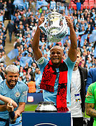 Vincent Kompany (4) of Manchester City lifts the FA Cup with his team mates during the trophy presentation during the The FA Cup Final match between Manchester City and Watford at Wembley Stadium, London, England on 18 May 2019.