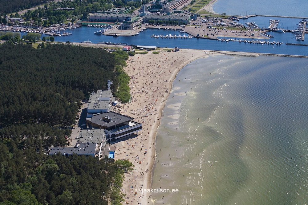 Apartment Building at Pirita River Mouth, Tallinn, Estonia. Forest with buildings. Waterfront. People on Beach, Baltic Sea.