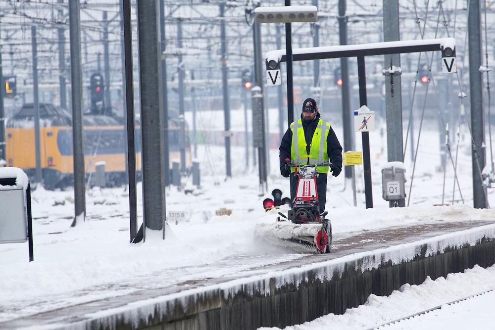 Een man maakt het perron op Utrecht CS sneeuwvrij, terwijl op de achtergrond de trein naar Leiden vertrekt. Het is een van de weinige treinen die op zondagochtend rijdt. Ondanks alle voorzorgsmaatregelen met een speciale dienstregeling, lukt het de NS en ProRail niet om de treinen vanuit Utrecht goed te laten rijden.<br /> <br /> A man is plowing the platforms at Utrecht CS, while one of the few trains is leaving the station. In spite of al the precautions the Dutch railways are having a lot of problems with the snowfall this winter.