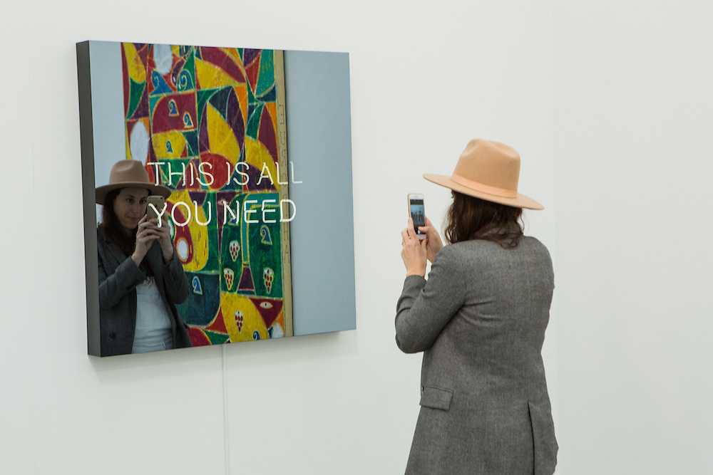 "New York, NY - 6 May 2016. Frieze New York art fair. A woman takes a photo of Jeppe Hein's ""This is all you need"", a reflective piece in Galleri Nicolai Wallner."