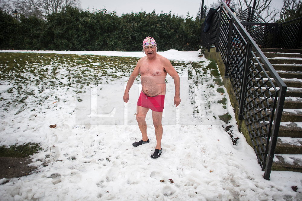 © Licensed to London News Pictures. 03/03/2018. London, UK. A members of the Serpentine Swimming Club prepares to roll in snow after braving freezing overnight temperatures as they enjoy an early morning race at sunrise in the Serpentine in Hyde Park, London. Large parts of the UK are recovering from a week of sub zero temperatures and heavy snowfall, following two severe cold fronts. Photo credit: Ben Cawthra/LNP