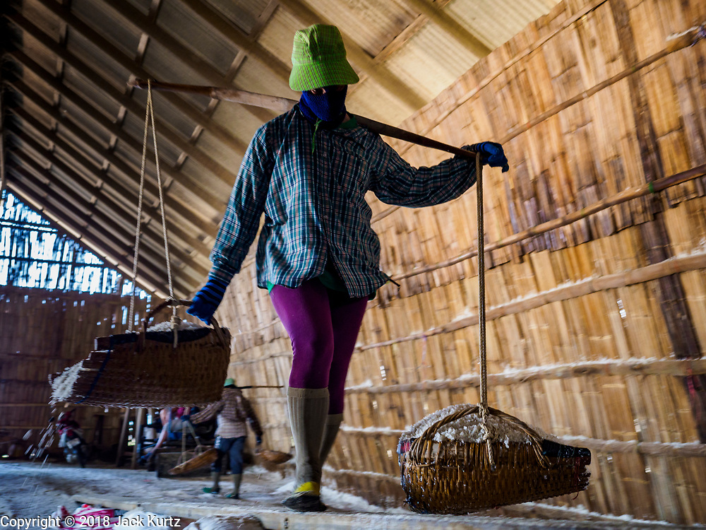 28 MARCH 2018 - BAN LAEM, PHETCHABURI, THAILAND: A worker brings freshly gathered salt into a warehouse during the 2018 salt harvest in Petchaburi province, about two hours south of Bangkok. Sea salt is made in provinces south of Bangkok by flooding fields with ocean water after the rainy season. As the fields dry out from evaporation, workers go into the fields and gather the salt left behind.        PHOTO BY JACK KURTZ