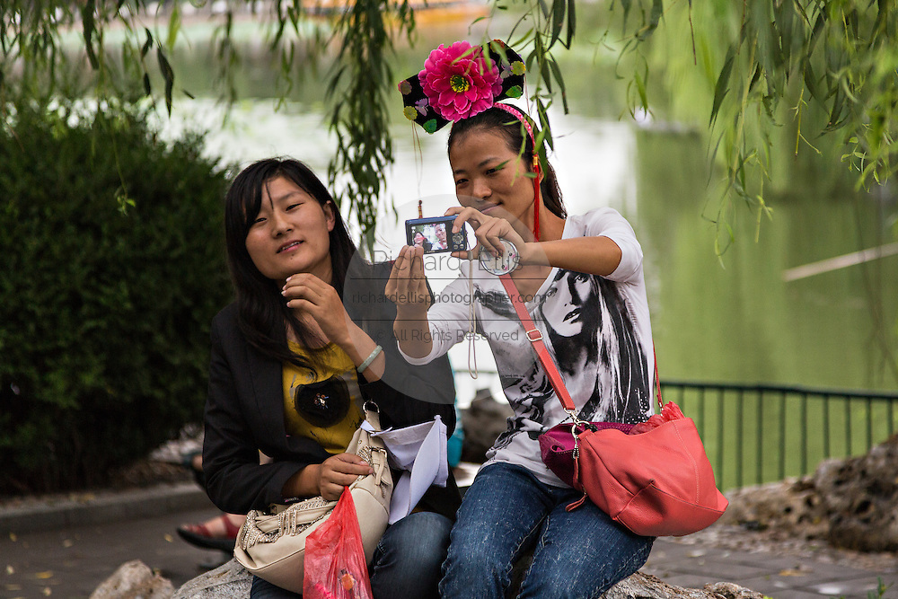 A woman has her picture taken wearing a traditional headdress at Beihai Park in Beijing, China