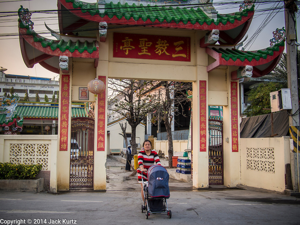 "25 JANUARY 2014 - BANG LUANG, NAKHON PATHOM, THAILAND: A performer with the Sing Tong Teochew opera troupe walks her baby across the street before a show in a Chinese shrine in the town of Bang Luang, Nakhon Pathom, Thailand. The Sing Tong Teochew opera troupe has been together for 60 years and travels through central Thailand and Bangkok performing for mostly ethnic Chinese audiences. Chinese opera was once very popular in Thailand, where it is called ""Ngiew."" It is usually performed in the Teochew language. Millions of Chinese emigrated to Thailand (then Siam) in the 18th and 19th centuries and brought their cultural practices with them. Recently the popularity of ngiew has faded as people turn to performances of opera on DVD or movies. There are still as many 30 Chinese opera troupes left in Bangkok and its environs. They are especially busy during Chinese New Year when travel from Chinese temple to Chinese temple performing on stages they put up in streets near the temple, sometimes sleeping on hammocks they sling under their stage.     PHOTO BY JACK KURTZ"