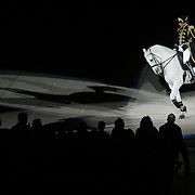 "A Lipizzaner  White Stallion prances in front of an audience in Des Moines, Iowa, during a show on their 37th Anniversary Tour in 2007. In 1970, Producer Gary Lashinsky created a new family arena attraction, starring The ""World Famous"" LIPIZZANER STALLIONS...Many horses and riders were brought from Europe to perform  for over twenty-three million people throughout North and South America, Great Britain, Europe, Australia and Hawaii have seen this internationally acclaimed spectacle.  ..choreography and music have been incorporated in this anniversary edition with a major emphasis on the historical background and foundation of the Lipizzaner breed, from its original breeding and use as a horse of war to a horse of nobility and aristocracy to a living form of equestrian art. The show emulates the Spanish Riding School of Vienna, Austria, in its presentation of Lipizzans, and maintains a traditional as well as entertaining performance similar in many ways to what you would see at the Spanish Riding School of Vienna...."