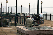 San Francisco, California, June, 2008-A homeless man sitting on a pier along the Embarcadero. The Bay Bridge is in the background.