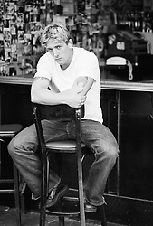 Young man sitting with arms crossed inside a bar