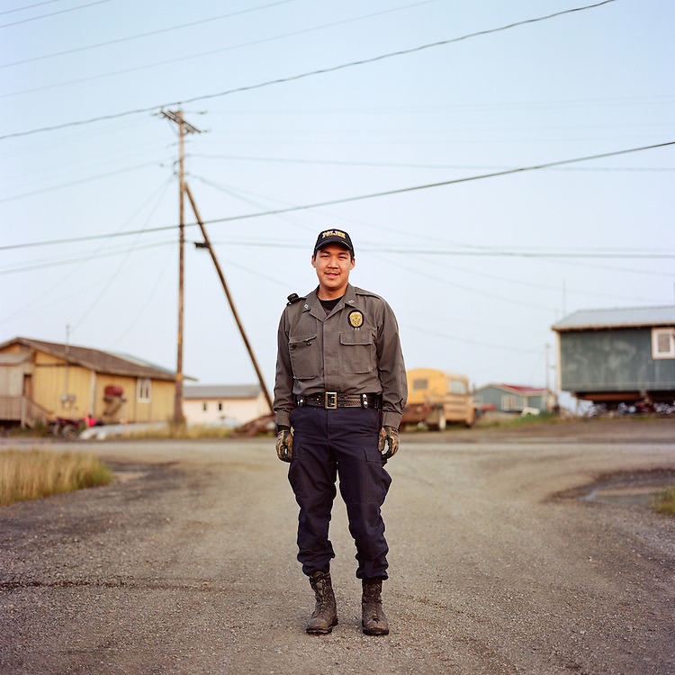 """""""I started this Monday. This is my first drunk call. I just want to help people, and make their lives better. I grew up here and in Bethel [Alaska].""""—Phillip Charlie is the Village Police Officer in Quinhagak, Alaska. In many villages throughout rural Alaska, the first responders to public safety emergencies are Village Police Officers and Village Public Safety Officers whose work is supervised by Alaska State Troopers located in the larger regional hub towns like Bethel. Village Police Officers, unlike police officers in cities throughout the country, do not carry firearms. In 2014, there was a change in Alaska State law that will allow Village Public Safety Officers to receive training to carry firearms."""