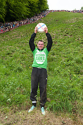 © Licensed to London News Pictures. 25/05/2015. Brockworth, Gloucestershire, UK.  Ryan Fairley age 25 from Brockworth wins the second mens' race for the third year in a row at the annual traditional Cheese Rolling races, which by custom take place on Bank Holiday Monday.  Participants race down the very steep Coopers Hill chasing a Double Gloucester Cheese, and injuries sometimes happen. Photo credit : Simon Chapman/LNP