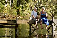 Senior Couple sitting on dock by lake.