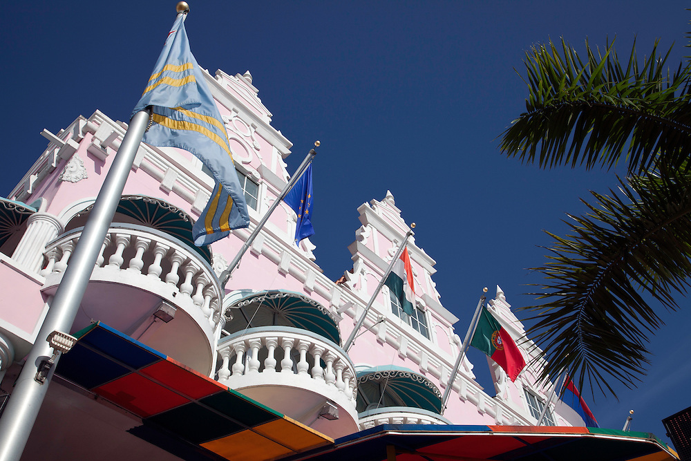 Aruba, Lesser Antilles.  Numerous colorful flags fly in front of one of Oranjestad's most elaborate buildings, a pleasant sight along the city's waterfront.  Ice cream-colors are a hallmark of the island's largest town, Oranjestad, usually within Dutch Colonial architectural design.