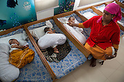 A young baby being fed whilst others sleep in the child care centre at an Epyllion Group garment factory in Dhaka, Bangladesh.