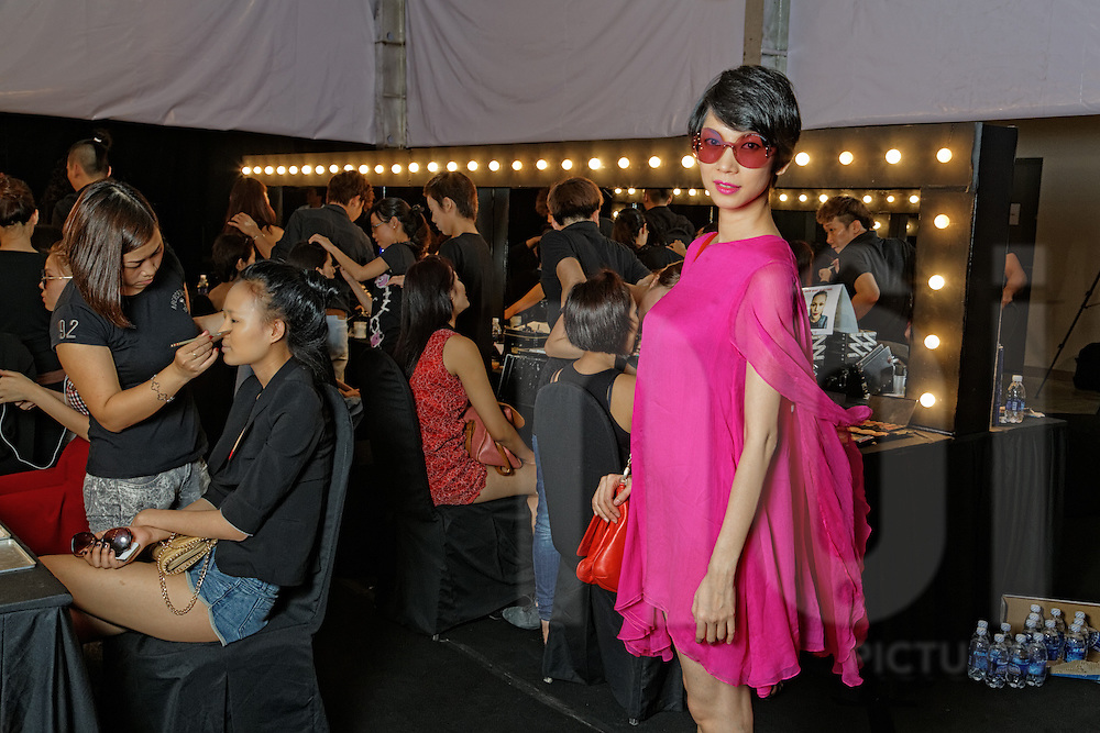 """A model in a pink dress poses backstage next to stylists as they put finishing touches on models during """"The Muse"""" fashion show by designer Do Manh Cuong, Ho Chi Minh City, Vietnam, Southeast Asia"""
