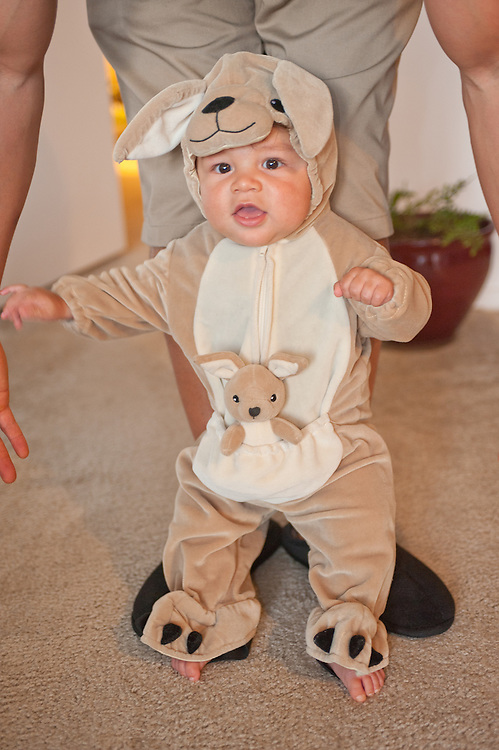 young child dressed in kangaroo costume taking his first steps, father supporting