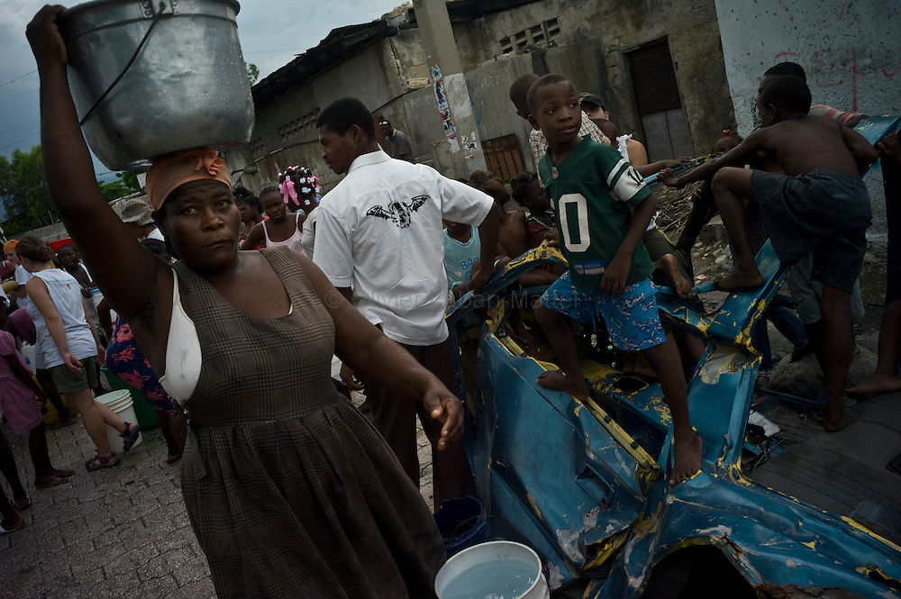 The number of cholera victims in Cité Soleil, a slum of Port-au-Prince, is increasing day by day exponentially, according to a doctor of Doctors Without Borders, essentially because of hygienic problems./// A woman carries a bucket of water while children play on a car body in a street of the slum of Cite Soleil in Port-au-Prince.