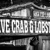 Live Crab and Lobster Sign on Dory Fish Market black and white picture. The Dory Fishing Fleet is part of the historic landmark Dory Fish Market in Newport Beach California.
