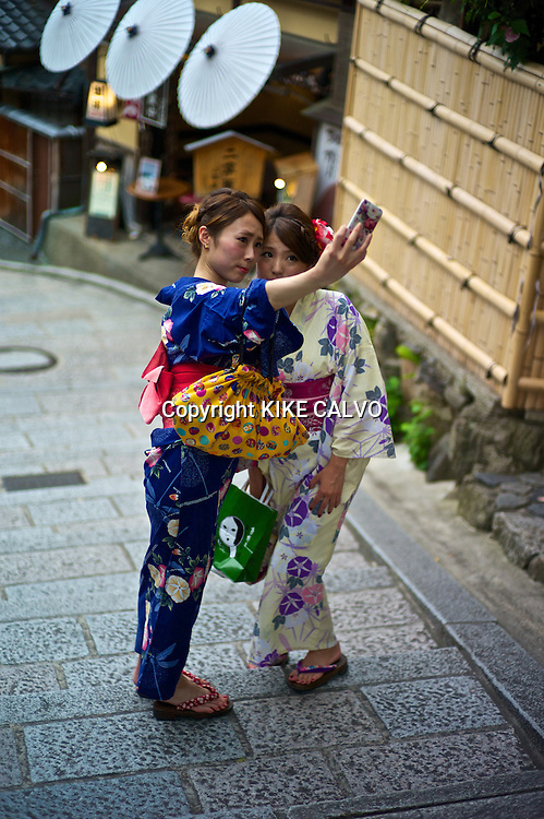 Asian women in traditional kimonos take a self-portrait using a cel phone near the Kiyomizu Temple.