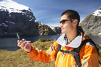 Hiker using compass in mountains