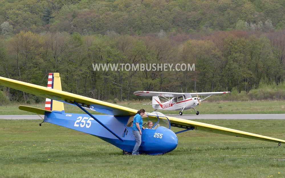 Wurtsboro, NY - An airport employee talks to a young girl in Schweizer SGS 2-33A glider before the girl takes a flight as a 1971 Bellanca 7ACA airplane gets ready to take off in the background at the grand reopening of Wurtsboro Airport on May 11, 2008.