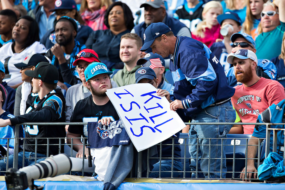 """NASHVILLE, TN - NOVEMBER 15:  Fan of the Tennessee Titans takes down a sign that says to """"Kill Isis"""" during a game against the Carolina Panthers at Nissan Stadium on November 15, 2015 in Nashville, Tennessee.  (Photo by Wesley Hitt/Getty Images) *** Local Caption ***"""