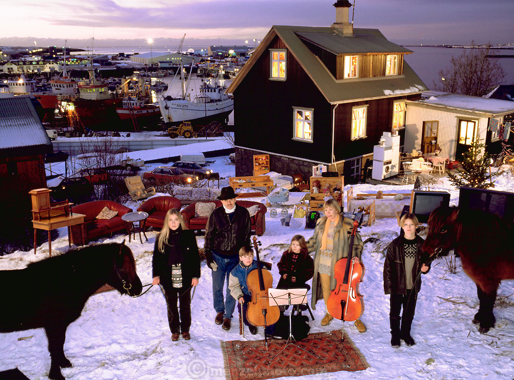 The Thoroddsen Family posed with all of their possessions in front of their home, Hafnarfjordur, Iceland. Published in the book Material World: A Global Family Portrait, pages 162-163. The Thoroddsen family lives in a 2,000 square foot wooden frame house overlooking the harbor in Hafnarfjordur, Iceland (near Reykjavik). Bjorn is a pilot for Iceland Air and Margaret (called Linda) is a milliner.