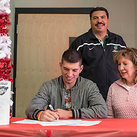 121914       Cable Hoover<br /> <br /> Former Gallup High School football player Dominic sits with his mother Barbara Martinez and father AL Martinez as he signs a letter of intent to play for South Dakota School of Mines and Technology Friday at Wingate High School.