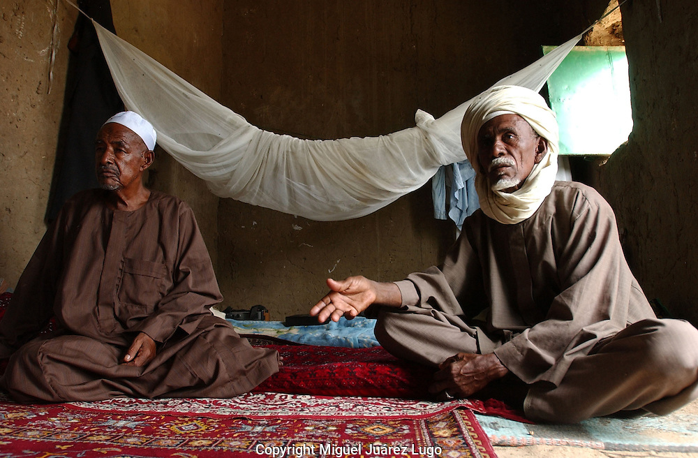 "Abu Gudam, Chad: Arab sheikh Al-Jhaly Yusuf, left, and cow herder Jama Burma, right, describe a crackdown by the Chadian government and its allied militias on Arab nomads over the past year.  Chadian Arab nomads, who have been broadly vilified as so-called ""janjaweed"" notorious for the violence in Darfur, say government soldiers have harassed and tortured them.Chad is home to over 200 different ethnic and linguistic groups. Arabic and French are the official languages. Islam and Christianity are the most widely practiced religions.  Chad is one of the poorest and most corrupt countries in the world; most inhabitants live in poverty as subsistence herders and farmers. Since 2003, crude oil has become the country's primary source of export earnings, superseding the traditional cotton industry. Chad is considered a failed state by the Fund for Peace. (PHOTO: MIGUEL JUAREZ LUGO)."