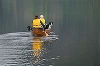 Paddlers in a canoe on Muchalat Lake near Gold River enjoy a leisurely outing while fishing with their dog.  Central Vancouver Island, British Columbia, Canada.