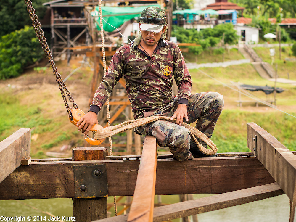 16 SEPTEMBER 2014 - SANGKHLA BURI, KANCHANABURI, THAILAND: A member of the Mon community works on the deck of the Mon Bridge. The 2800 foot long (850 meters) Saphan Mon (Mon Bridge) spans the Song Kalia River. It is reportedly second longest wooden bridge in the world. The bridge was severely damaged during heavy rainfall in July 2013 when its 230 foot middle section  (70 meters) collapsed during flooding. Officially known as Uttamanusorn Bridge, the bridge has been used by people in Sangkhla Buri (also known as Sangkhlaburi) for 20 years. The bridge was was conceived by Luang Pho Uttama, the late abbot of of Wat Wang Wiwekaram, and was built by hand by Mon refugees from Myanmar (then Burma). The wooden bridge is one of the leading tourist attractions in Kanchanaburi province. The loss of the bridge has hurt the economy of the Mon community opposite Sangkhla Buri. The repair has taken far longer than expected. Thai Prime Minister General Prayuth Chan-ocha ordered an engineer unit of the Royal Thai Army to help the local Mon population repair the bridge. Local people said they hope the bridge is repaired by the end November, which is when the tourist season starts.    PHOTO BY JACK KURTZ