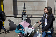 A family walk past Evening Standards with Prime Minister Theresa May on the front page, asking the nation to trust her and yesterday's snap election announcement, outside the Bank of England in the heart of the capital's financial district, on 19th April, in the City of London, England.