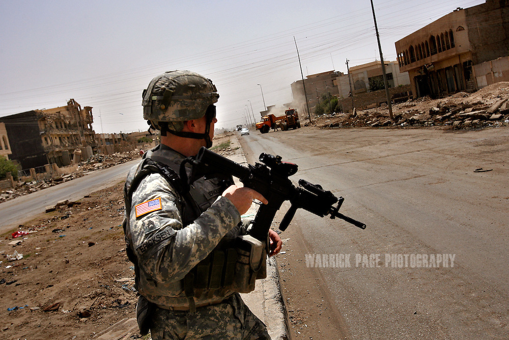 MOSUL, IRAQ - JULY 10: Sgt 1st Class Thomas Ericksen (30) of 3rd Squadron, 3rd Armored Cavalry Regiment from Ohio, crosses Baghdad Highway as construction crews clear rubble and debris caused from frequent street battles with Al Qaeda insurgents, July 10, 2008, Mosul, Iraq. Iraqi officials declared Mosul the last urban stronghold of Al Qaeda in Iraq. Only months ago, Mosul was the communication and supply hub for Al Qaeda and other insurgent groups from the Syrian border to central Iraq before US and Iraqi forces pushed them into the rural, desert areas where they are believed to be regrouping in the western Jazeera desert. With the upcoming provincial elections in autumn, Iraqis and Americans are bracing themselves for renewed violence. Since early 2008, Iraq's security situation has improved with oil production increasing, record government surplus and easing sectarian tensions. (Photo by Warrick Page)