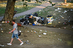 © Licensed to London News Pictures. 27/08/2019. London, UK. A man walks through rubbish and debris strewn across a public park in Notting Hill, west London, in the aftermath of the 2019 Notting Hill carnival. The two day event is the second largest street festival in the world after the Rio Carnival in Brazil, attracting over 1 million people to the streets of West London. Photo credit: Ben Cawthra/LNP