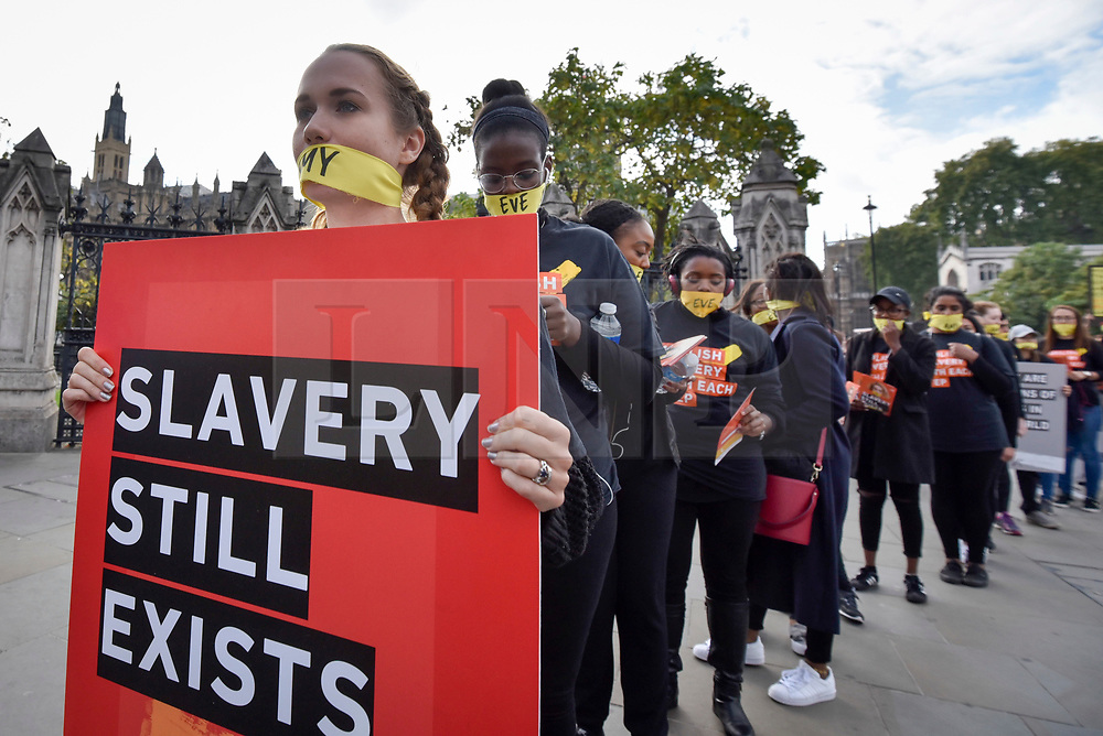 """© Licensed to London News Pictures. 14/10/2107. London, UK. People take part in the """"The Walk For Freedom"""", marching around the capital demonstrating against modern slavery.  The protest is co-ordinated with other walks which abolitionist group A21 is staging in 400 cities around the world on the same day. The facemasks represents the silence of modern slaves. Photo credit : Stephen Chung/LNP"""
