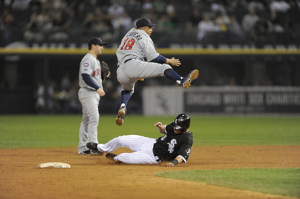CHICAGO - SEPTEMBER 23:  Orlando Cabrera #18 of the Minnesota Twins turns a double play over a sliding Jayson Nix #5 of the Chicago White Sox on September 23, 2009 at U.S. Cellular Field in Chicago, Illinois.  The Twins defeated the White Sox 8-6.  (Photo by Ron Vesely)