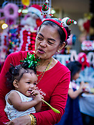 "23 DECEMBER 2018 - CHANTABURI, THAILAND: A woman plays with her granddaughter while they wait for the Christmas Fair to start at the Cathedral of the Immaculate Conception in Chantaburi. Cathedral of the Immaculate Conception is holding its annual Christmas festival, this year called ""Sweet Christmas @ Chantaburi 2018"". The Cathedral is the largest Catholic church in Thailand and was founded more than 300 years ago by Vietnamese Catholics who settled in Thailand, then Siam.  PHOTO BY JACK KURTZ"