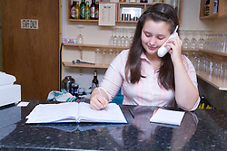 Young Polish woman taking a telephone booking for a meal at a Polish restaurant,