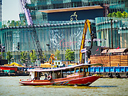 02 NOVEMBER 2018 - BANGKOK, THAILAND: A tug boat goes up the Chao Phraya River past the ICONSIAM development. ICONSIAM is supposed to open November 9, the new Apple Store logo is near the top of the frame. The logo is a blend of the traditional Apple logo and the Thai word for apple. ICONSIAM is a mixed-use development on the Thonburi side of the Chao Phraya River. It will include two large malls, with more than 520,000 square meters of retail space, an amusement park, two residential towers and a riverside park. It is the first large scale high end development on the Thonburi side of the river and will feature the first Apple Store in Thailand and the first Takashimaya department store in Thailand.    PHOTO BY JACK KURTZ