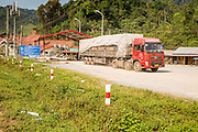 13 MARCH 2013 - ALONG HIGHWAY 13, LAOS: Trucks near the end of Highway 13 in the Boten Special Economic Zone. The SEZ is in Laos immediately south of the Lao Chinese border. It has turned into a Chinese enclave but many of the businesses struggle because their goods are too expensive for local Lao to purchase. Some of the hotels and casinos in the area have been forced to close by the Chinese government after reports of rigged games. The paving of Highway 13 from Vientiane to near the Chinese border has changed the way of life in rural Laos. Villagers near Luang Prabang used to have to take unreliable boats that took three hours round trip to get from the homes to the tourist center of Luang Prabang, now they take a 40 minute round trip bus ride. North of Luang Prabang, paving the highway has been an opportunity for China to use Laos as a transshipping point. Chinese merchandise now goes through Laos to Thailand where it's put on Thai trains and taken to the deep water port east of Bangkok. The Chinese have also expanded their economic empire into Laos. Chinese hotels and businesses are common in northern Laos and in some cities, like Oudomxay, are now up to 40% percent. As the roads are paved, more people move away from their traditional homes in the mountains of Laos and crowd the side of the road living off tourists' and truck drivers.    PHOTO BY JACK KURTZ