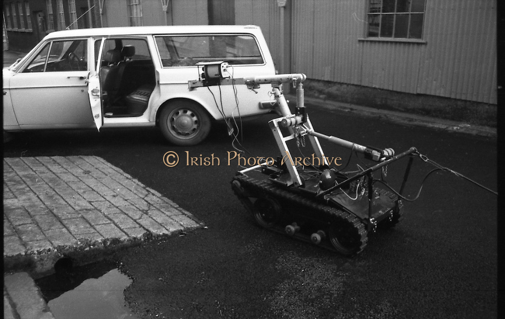 Bomb Disposal Robot.   (J97)..1975..29.12.1975..12.29.1975..29th December 1975..At Clancy Barracks,Dublin the Irish army put on display their newly aquired Bomb Disposal Robot. It would be invaluable in inspecting suspect buildings or vehicles. The series of pictures shows the army demonstration of the equipment..Image shows the robot approaching the suspect vehicle to inspect for potential explosive devices.