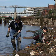 Mudlarkers look for items on the banks of the River Thames in London, Britain May 22, 2016. When the river Thames is at low tide, mudlarkers scour the shore for historical artefacts and remains from there City of London's ancient past. Finds can date back to Roman times to when the city was found up until more recent times. Anyone can walk along the river and look for finds, but the uses of metal detectors and digging is restricted. Mudlarkers need to be licences by the Port of London Authority. All find should be register with the Museum of London. REUTERS/Neil Hall