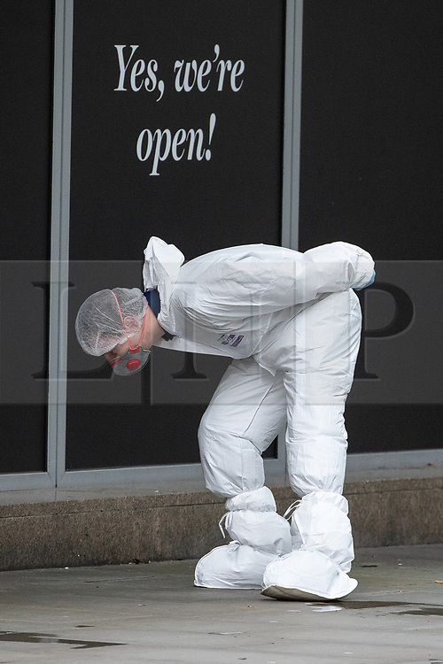 © Licensed to London News Pictures. 11/10/2019. Manchester, UK. A forensic scenes of crime examiner searches the pavement in front of Marks and Spencer at the scene . Terrorism Police are investigating after four people were stabbed during a single attack at the Arndale Centre in Manchester City Centre . Photo credit: Joel Goodman/LNP